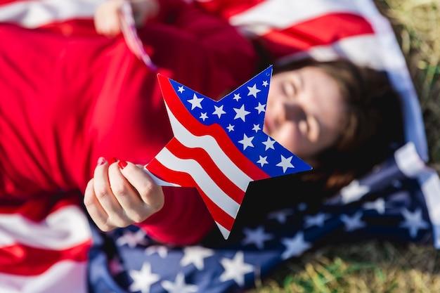 Liggende vrouw die de vlagachtergrond van de vs houdt en camera bekijkt