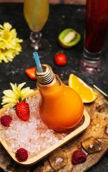 Light bulb glazen flessen met verse oranje tropische vruchten sap op plaat met ijsblokjes en strawbesrries. vakantie ontspanning detox reiniging wellness