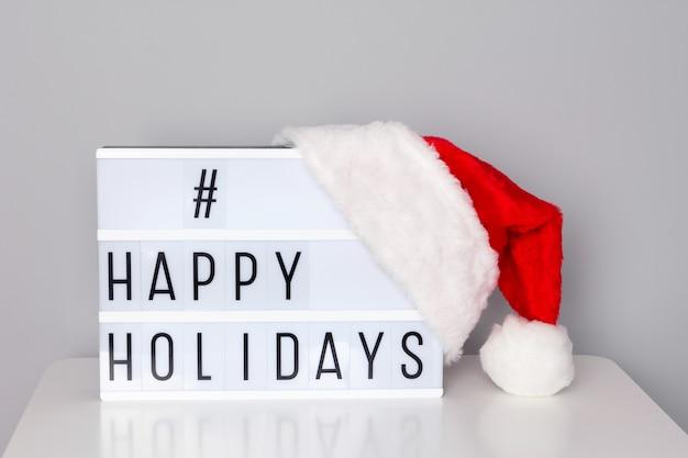 Lightbox met happy holidays hashtag-tekst en rode kerstmuts op witte tafel bij de muur