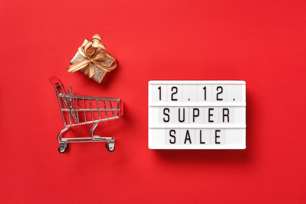 Lightbox met tekst, gouden geschenkdoos en winkelwagen op rode achtergrond. dubbele 12 mega-verkoopdag plat lay-promotiesamenstelling.