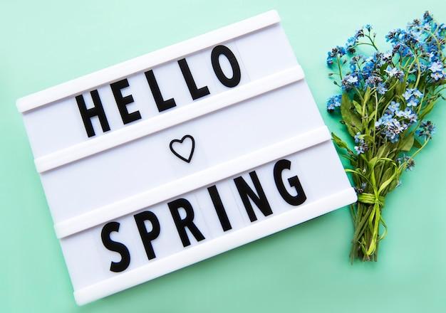 Lightbox met tekst hello spring en boeket vergeet me niet bloemen op groen, bovenaanzicht