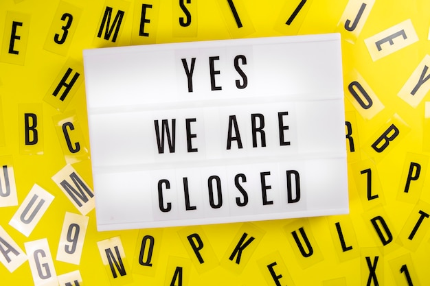Lightbox met tekst ja we zijn gesloten op gele achtergrond met letters eromheen