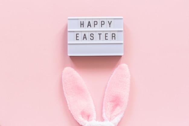 Lightbox-tekst gelukkige pasen en konijntjesoren op roze document achtergrond.