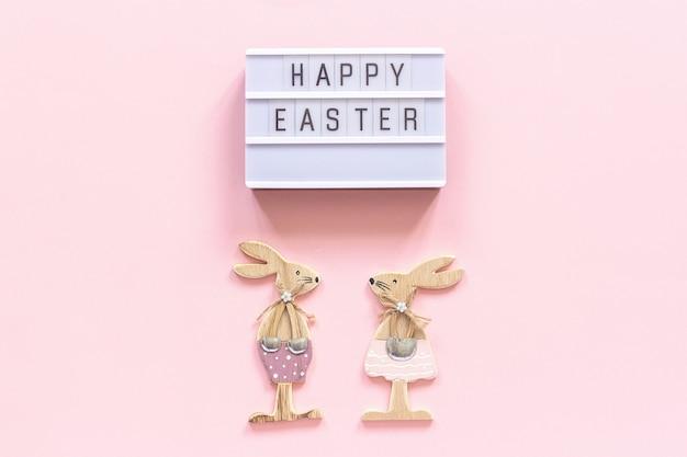 Lightbox-tekst gelukkige pasen en paar houten konijntjes op roze document achtergrond.