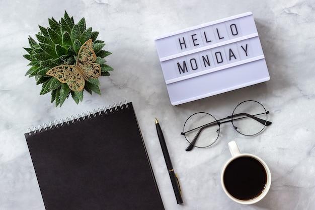 Lightbox tekst hallo maandag zwarte notitieblok, kopje koffie, succulent, bril concept stijlvolle werkplek