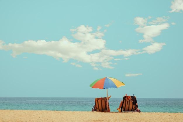 Ligstoel op tropisch strand met kalme hemel
