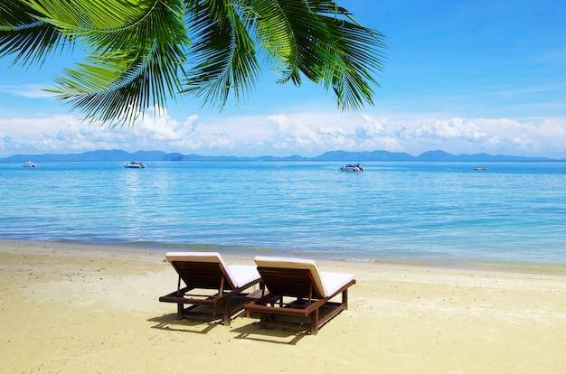 Ligstoelen aan de kust. strand en tropische zee. zomervakantie concept
