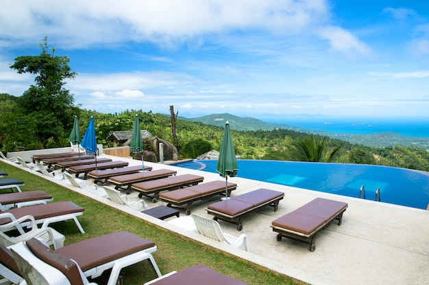 Ligstoelen bij het zwembad van een luxe hotel met uitzicht op zee