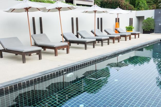 Ligstoelen dichtbij zwembad in hotel