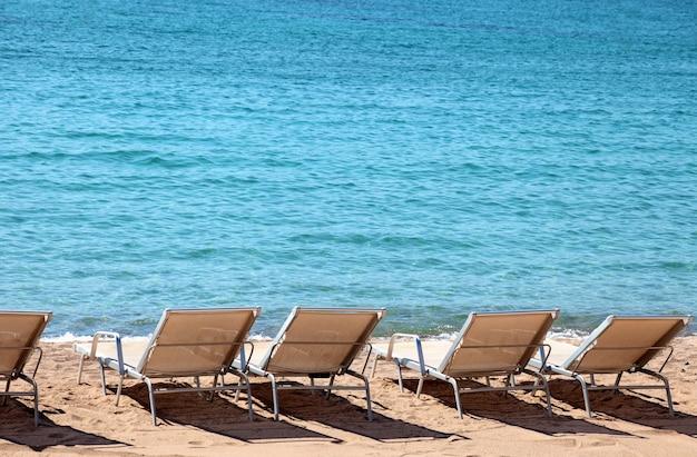 Ligstoelen in een rij op een zonnige dag