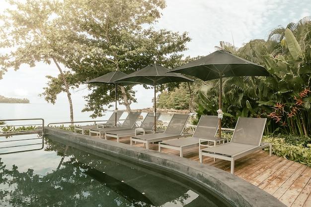 Ligstoelen met parasol in de buurt van het zwembad