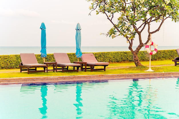 Ligstoelen met parasol rond zwembad