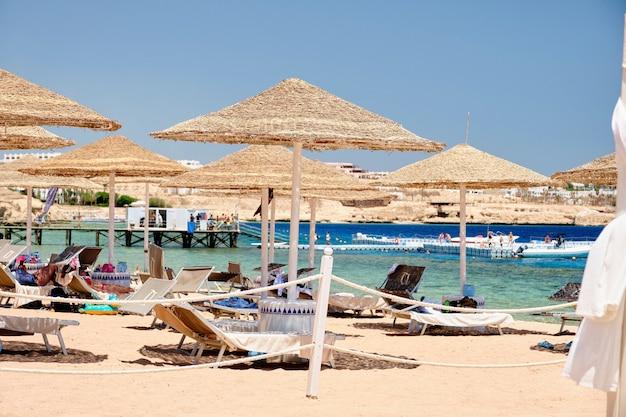 Ligstoelen met parasols op het strand voor een ontspannen vakantie op de achtergrond van de zee.