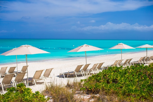 Ligstoelen op exotisch tropisch wit zandstrand