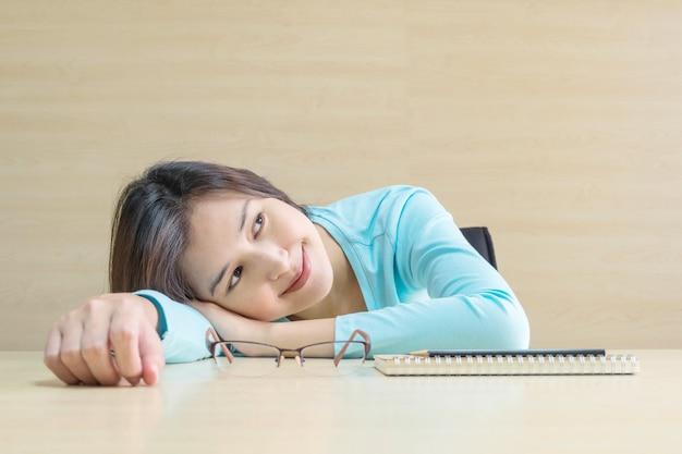 Ligt de close-up aziatische vrouw op bureau met gelukkig gezicht in rust van het lezen van een boek op vaag houten bureau