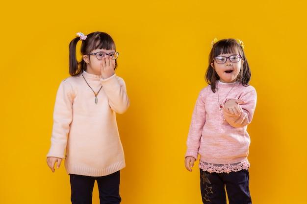 Lijdend aan abnormaliteit. kleine mooie meisjes met een psychische stoornis die roze truien en een heldere bril dragen voor een beter zicht