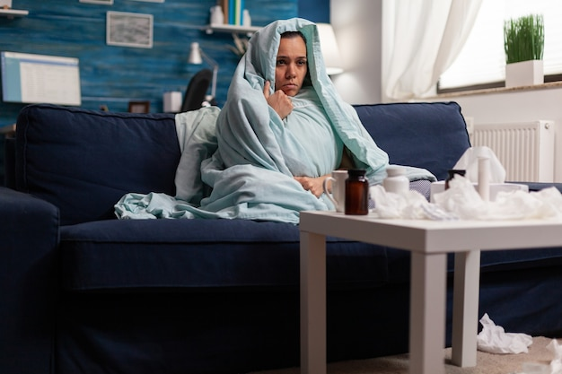 Lijdende vrouw in deken die zich thuis ziek voelt met seizoensgebonden virusinfectiesymptomen. onwel blanke jonge persoon die op de bank rust met hoofdpijn door ziekte, gewikkeld in een deken