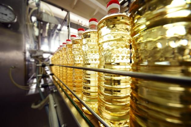Lijn of transportband voor voedselproductie van zonnebloemolie. flessen met plantaardige olieclose-up tegen het oppervlak van fabrieksapparatuur