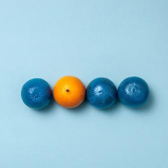 Lijn van blauwe sinaasappels met één schone sinaasappel