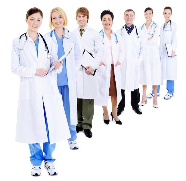 Lijn van groep gelukkige artsen in ziekenhuisjassen die op wit worden geïsoleerd
