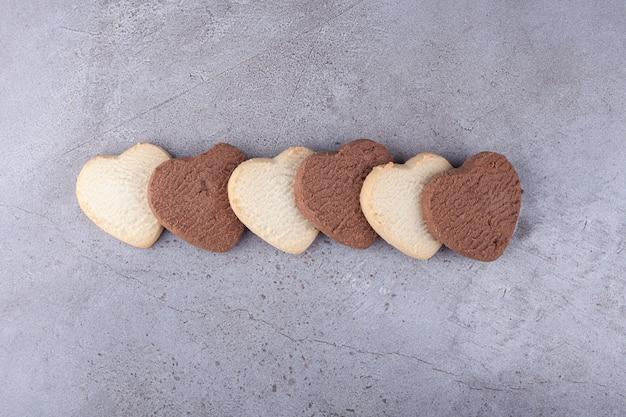 Lijn van hartvormige koekjes geplaatst op een stenen achtergrond.