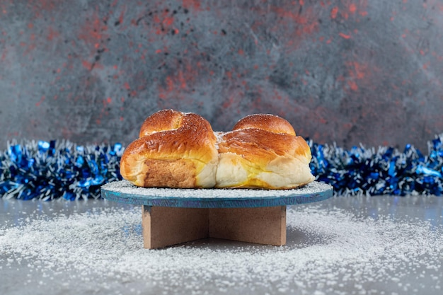 Lijn van klatergoud achter een zoet broodje op een standaard op marmeren tafel. Gratis Foto