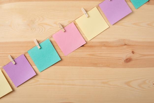 Lijn van kleurrijke notities op de draad tegen houten