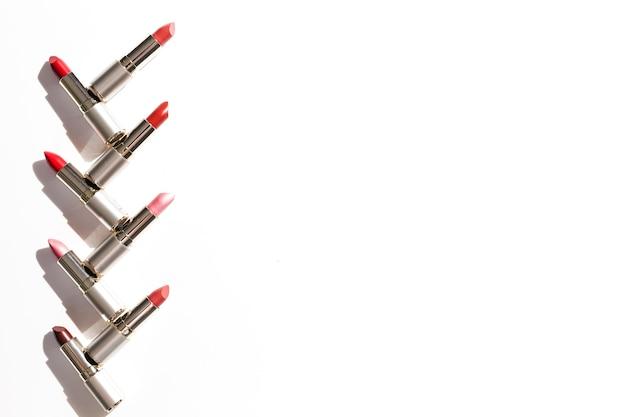 Lijn van metaallippenstiften op witte achtergrond