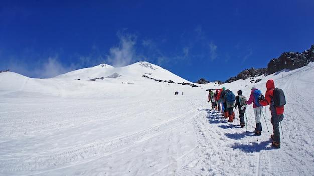 Lijn van toeristenmensen met apparatuur die naar de berg elbrus stijgen. grote hoogte en top aan de horizon