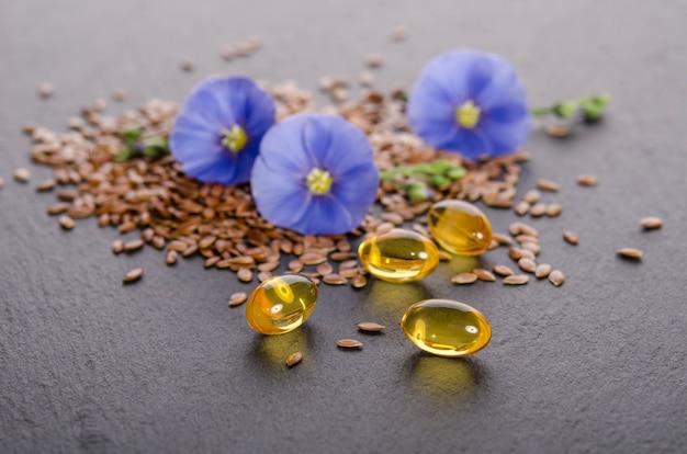 Lijnzaad, schoonheidsbloem en olie in doppen op grijs. fytotherapie.