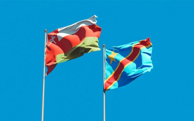 Lijst van vlaggen van oman en dr congo op blauwe hemel. 3d-illustraties
