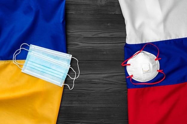 Lijst van vlaggen van rusland en oekraïne op houten achtergrond met medische maskers, coronavirus-concept