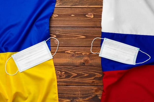 Lijst van vlaggen van rusland en oekraïne op houten achtergrond met medische maskers