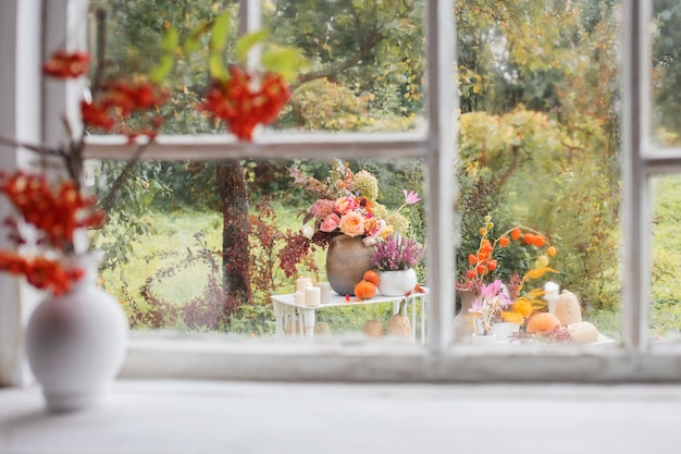 Lijsterbessen in witte vaas op oude witte vensterbank