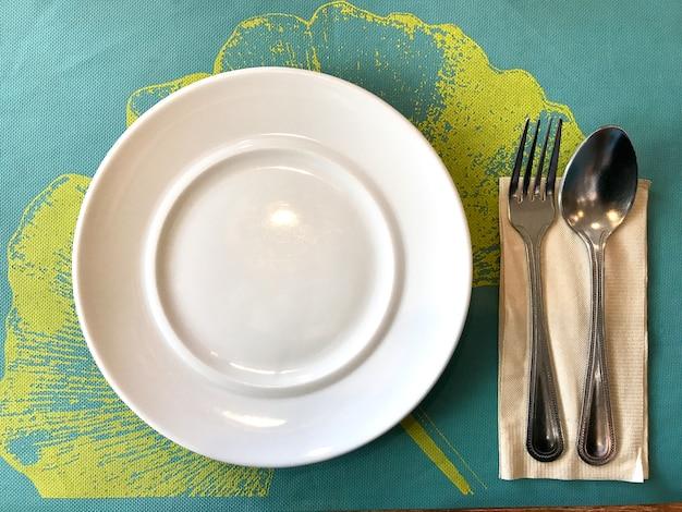 Lijstreeks, schotel, lepel en vork op het blauwe onderleggertje hoogste mening