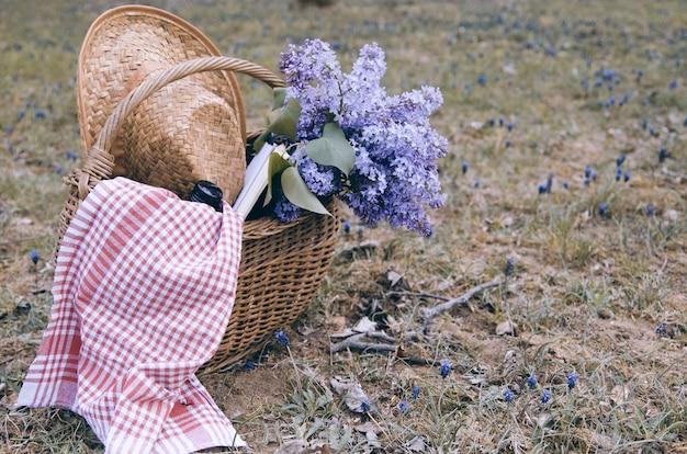 Lila bloemboeket in rieten mand met picknickbehoefte