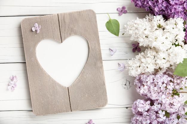 Lila bloemen achtergrond met lege hartvormige fotolijstjes, close-up