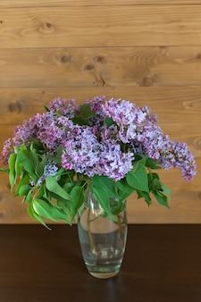 Lila bloemen in transparante glazen vaas. charmant boeket van bloeiende sering in de keuken.