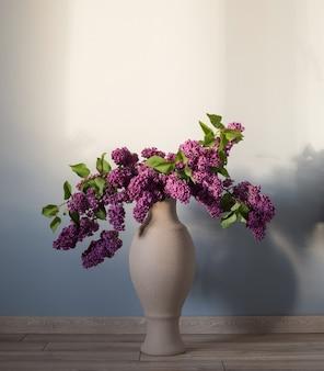 Lila bloemen in vaas op houten vloer