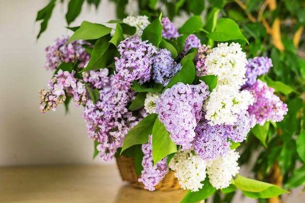 Lila bloementakken in rieten mand op houten tafel in de buurt van witte muur
