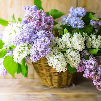 Lila bloementakken in rieten mand op natuurlijke houten tafel in de buurt van muur