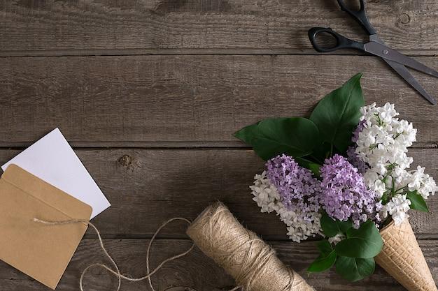 Lila bloesem op rustieke houten achtergrond met lege ruimte voor begroeting. schaar, draadspoel, kleine envelop. lente achtergrond concept.