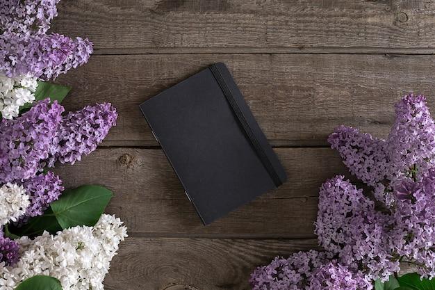Lila bloesem op rustieke houten achtergrond met notitieboekje voor begroeting bovenaanzicht