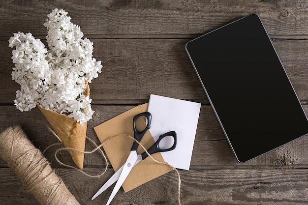 Lila bloesem op rustieke houten achtergrond tablet met lege ruimte voor begroeting schaar drie...