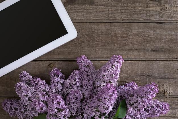 Lila bloesem op rustieke houten tablet als achtergrond met lege ruimte voor het bovenaanzicht van het begroetingsbericht