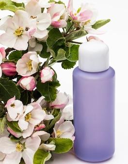 Lila cosmetische fles met peer bloemen op een witte achtergrond. natuurlijke biologische cosmetica concept.