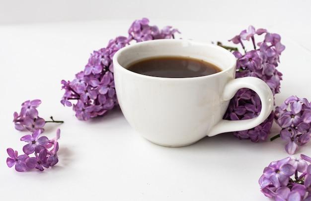 Lila en kopje koffie in vlakke stijl op witte houten achtergrond. mooie lente. bovenaanzicht. plat leggen, bovenkant. zomerseizoen. natuurlijke lentestijl.