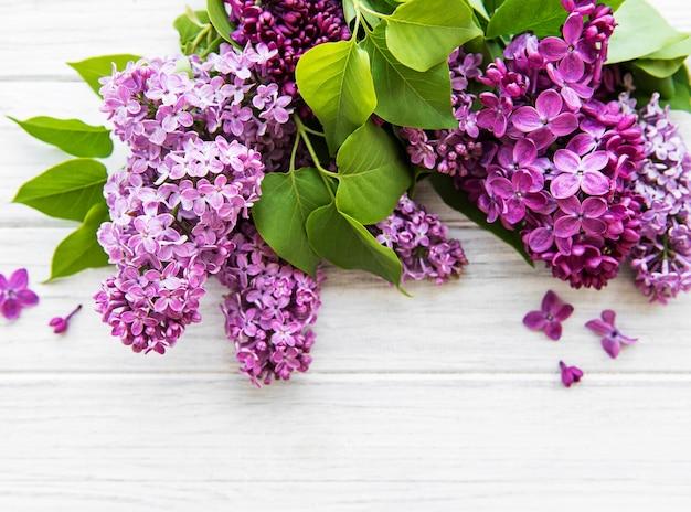 Lila in vlakke stijl op witte houten achtergrond. prachtige lente. bovenaanzicht. plat leggen, top. zomerseizoen. natuurlijke lentestijl.