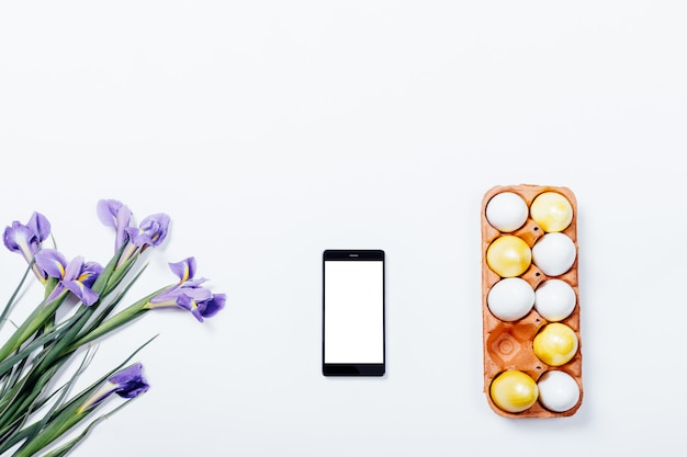 Lila irissen, mobiele telefoon en dienblad met beschilderde paaseieren