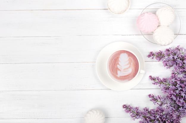 Lila, koffie met latte kunst en marshmallow op witte houten tafel. romantische ochtend. plat liggen